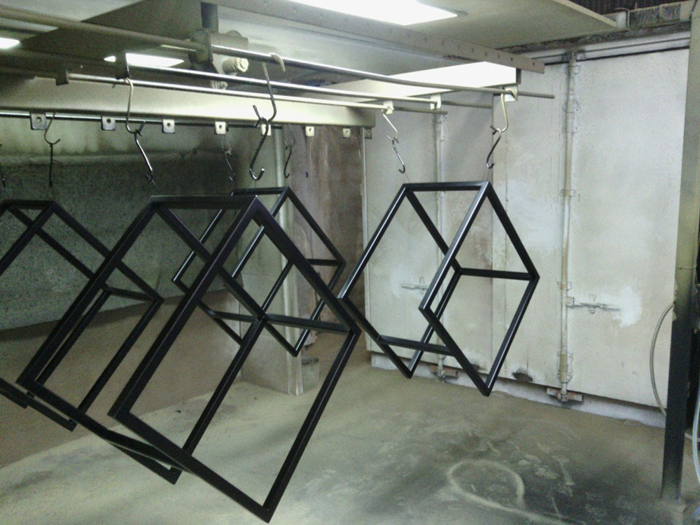 Multiple products that have gone though the powder coating conveyor belt hanging to dry