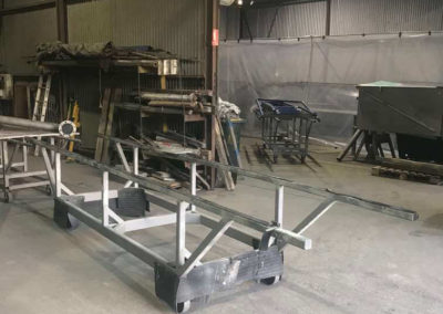 Purpose built trolleys used for transporting item into the blasting room then surface coating room and then to drying rooms.Carrying an elbow pipe riser which has been blasted by class 3 to raw steel