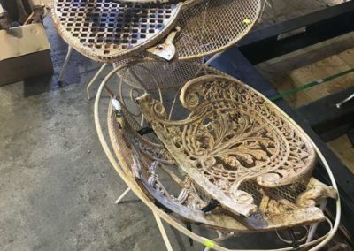 A pair of wrought iron latticed tables that have not yet been abrasive blasted. These to are a part of the home pick up and delivery service offered by Hartech
