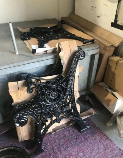 The two cast iron lacework ends of a garden bench that have been abrasive blasted undercoated and then powder coated black.