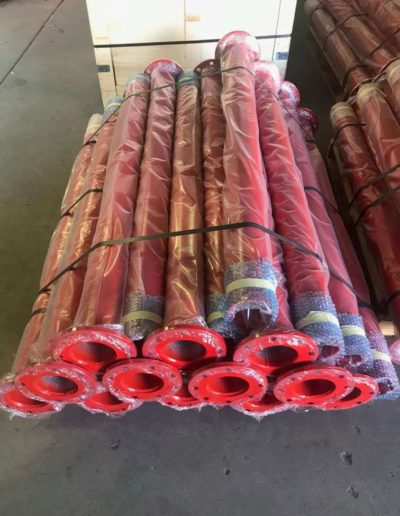 Straight gas pipes in standard length that have been abrasive blasted under-coated, surface coated a safety red colour wrapped in plastic ready for shipment