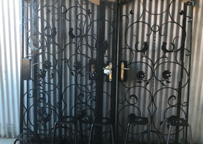 A set of 4 ornate gates and 4 stools that have been restored shown here with the the finishing black powder coating drying