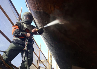 Abrasive blasting work being conducted on the hull of the the One and All Tall ship