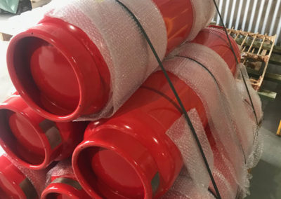 Industrial large fire extinguishers that have been resprayed red, loaded on a pallet ready for delivery